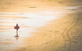 femme sur la plage avec planche de surf photo