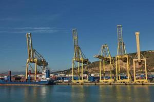 Grue portuaire charge un conteneur sur la jetée pour le transport d'import-export et de logistique d'entreprise à Barcelone, Espagne photo