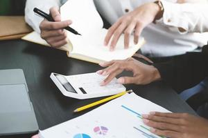 deux jeunes dirigeants d'entreprise discutent de changer leur concept d'entreprise pour augmenter les bénéfices et la force de leur entreprise en utilisant une calculatrice et un ordinateur portable pour le travail. photo