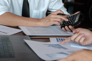 discussions de recherche économique, équipe commerciale analysant les tableaux et les graphiques des revenus pour planifier le concept de marketing à l'aide de la calculatrice pour l'analyse. photo