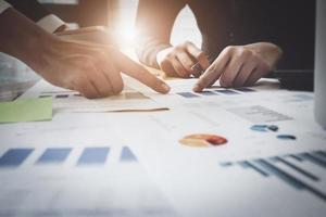 discussions d'affaires économiques, équipe commerciale analysant les tableaux et graphiques des revenus pour planifier le concept de marketing avec l'utilisation d'un ordinateur portable pour l'analyse. photo
