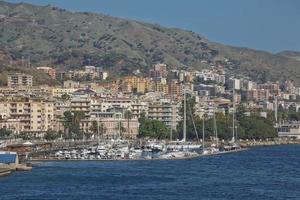Vue sur le port de Messines avec la statue d'or de la Madonna della Lettera en Sicile Italie photo