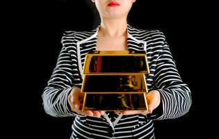 femme d & # 39; affaires tenant des lingots d & # 39; or sur fond noir photo