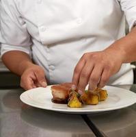 Chef décorant un repas traditionnel péruvien appelé chicharron de panceta de cerdo photo