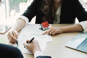 gros plan de femme d'affaires et de client pointant et signant un accord pour l'achat d'une maison. concept de directeur de banque. photo