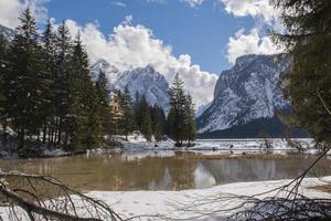lac alpin entre forêt et montagnes enneigées photo