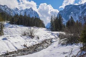 ruisseau entre la neige et les sommets photo