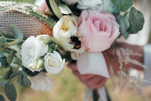 bouquet de mariée de mariage dans le style rustique sur lequel l'abeille est assise photo