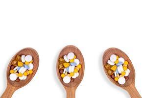 Pilules de médecine dans des cuillères en bois sur fond blanc avec copie espace photo
