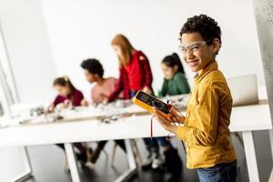 Mignon petit garçon debout devant les enfants de la programmation de jouets électriques et de robots en classe de robotique photo