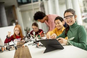 Des enfants heureux avec leur professeur de sciences afro-américaine avec des jouets électriques et des robots de programmation pour ordinateur portable à la classe de robotique photo