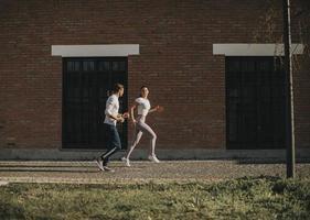 jeune couple en cours d'exécution dans l'environnement urbain photo