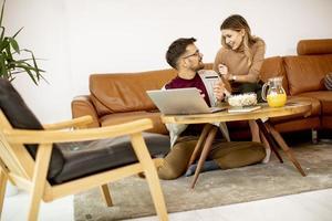 Jeune femme et jeune homme utilisant un ordinateur portable pour le paiement en ligne alors qu'il était assis par un canapé à la maison photo