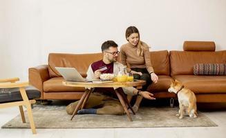 Jeune femme et jeune homme utilisant un ordinateur portable pour le paiement en ligne alors qu'il était assis par un canapé avec leur chien shiba inu à la maison photo