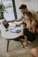 jeune femme et jeune homme utilisant un ordinateur portable alors qu'il était assis par un canapé à la maison photo
