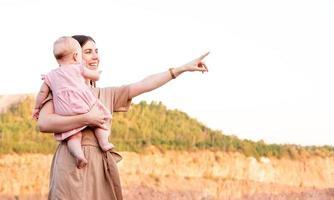 Heureuse mère tient bébé fille à la recherche de suite et pointant photo