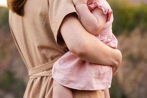 une jeune mère regarde la carrière ou les montagnes et tient un enfant dans ses bras photo