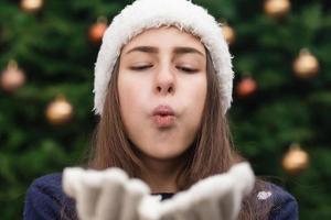 Noël belle femme soufflant un baiser à vous sur fond de sapin de Noël photo