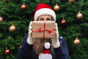 Une jeune fille portant un chapeau de père Noël donne un cadeau en papier kraft avec un ruban rouge photo