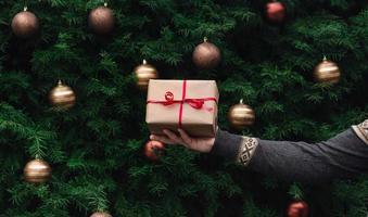 La main masculine en pull tricoté détient une boîte-cadeau en papier kraft photo