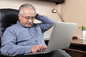 homme d'affaires senior pensif travaillant à la maison photo