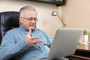 vieil homme fait un appel vidéo en parlant avec des parents ou des amis par application de vidéoconférence photo
