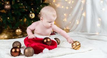Adorable bébé sans vêtements sur chapeau de père Noël sur fond de boules de Noël photo