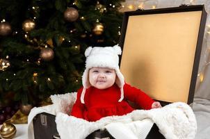le bébé grimace assis dans une vieille valise photo