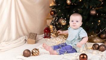 un bébé en jean est assis près d'un arbre de Noël et joue avec une guirlande dans laquelle il est empêtré photo