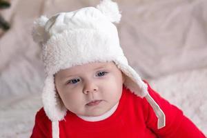 une jolie petite fille dans une robe rouge et un chapeau blanc exprime des émotions photo