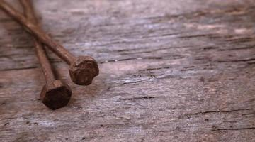 Deux vieux clous rouillés reposent sur un fond de bois photo