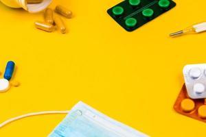 Masque de protection médicale en coton bleu sur fond de papier jaune avec des pilules photo