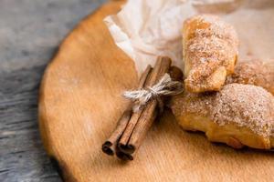 Croissants frais à la cannelle sur papier froissé sur table de fond en bois photo