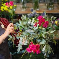 Fleuriste femme faisant un bouquet de fleurs au magasin photo