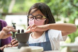 Gros plan du visage sale d'une fille asiatique avec des lunettes, apprendre à mouler l'argile dans une salle de classe. photo