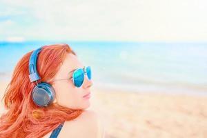belle femme à lunettes de soleil, écouter de la musique sur la plage photo