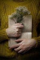 femme en pull tient un livre et un bouquet photo