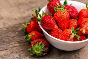 Bol plein de fraises fraîches sur une table brune photo