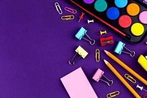 Fournitures de bureau scolaire papeterie sur fond violet photo