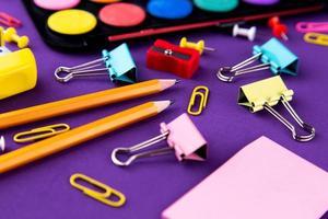 Fournitures de bureau de l'école de la papeterie sur un fond violet 24 retour au concept de l'école photo