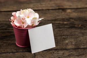 Fleurs d'hortensia rose pastel dans un petit seau et un morceau de papier sur fond de bois photo