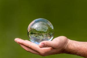 Boule de verre avec des arbres du lac en miroir et le ciel se trouve dans une main sur fond vert photo