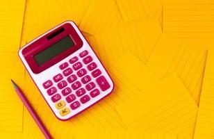 calculatrice sur feuilles de papier orange avec un crayon photo