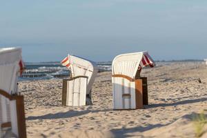 Des chaises de plage se tiennent au coucher du soleil sur une plage de la mer baltique avec mer photo