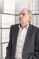 Homme d'âge moyen avec chemise blanche est debout devant un mur d'étagère avec des documents photo