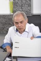 Senior homme avec une chemise blanche remet un dossier de fichiers photo