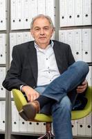 Homme mûr avec chemise blanche assis devant un mur d'étagère avec dossier de documents photo