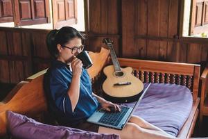 Femme ayant un café assis sur un étage à la maison en écrivant des notes ordinateur portable ouvert devant son concept de bureau à domicile photo