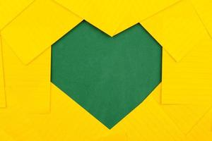 Feuilles de papier orange sur une commission scolaire verte forment un cadre en forme de coeur photo
