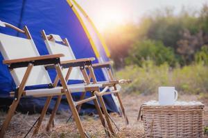 Tente de camping avec une tasse de café sur le bureau et des chaises en forêt le matin photo